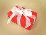 Ręczne pakowanie prezentu - biała wstążka z kwiatkami, całość zapakowane w ozdobny papier koloru czerwonego